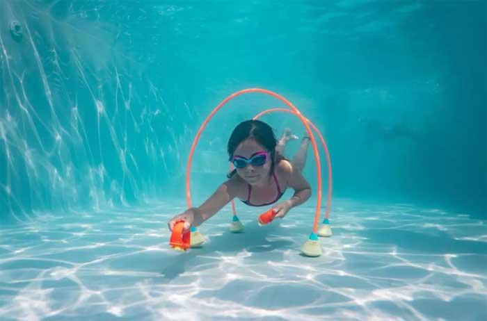onderwater parcours uitzetten voor waterspelletjes in zwembad op vakantie
